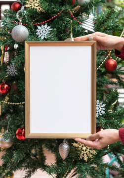 Hand holding mockup photo frame on christmas tree background. can be used for display or montage your message.