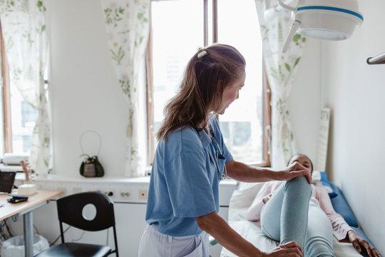 Female nurse examining patient's leg at clinic