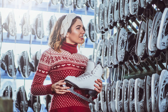 A charming girl wearing a warm sweater choosing a pair of skates