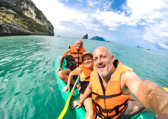 Senior mother and father with son taking selfie at kayak excursion in Thailand - Adventure travel in south east asia - Elderly and family concept of love sharing moments with parents - Warm vivid look Fotobehang