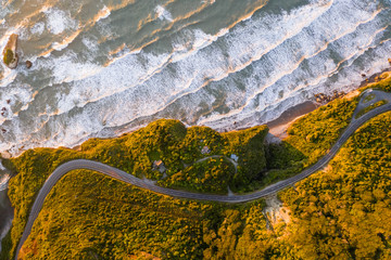 Aerial view of road crossing coastal cliff formation at Nine Mile, West Coast during the sunset, New Zealand.