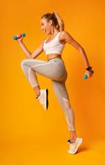 Excited Girl Jumping Holding Dumbbells Exercising In Studio, Full Length