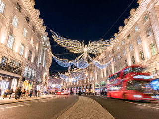 Foto op Aluminium Londen rode bus Angelic decorations illuminated and red double decker bus in motion on Regents street of London in Chrtistmas holiday, England