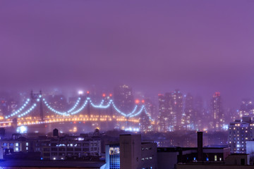 Ed koch Queensboro bridge with lights in misty weather in New York, NY, USA