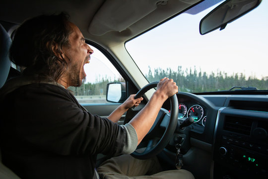 Side view photo of adult middle aged male with long dark hair driving his truck car through nature scenes while yawning and being very tired