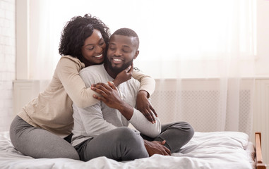 Happy african american spouses cuddling on bed at home