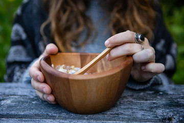 Selective focus and closeup photo of a person having lunch or dinner eating a healthy meal inside of a wooden bowl standing on a table