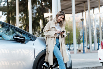 Young blond woman using smartphone, leaning on a car