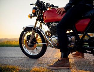 Crop shot of man on his motorbike at sunset, Tuscany, Italy