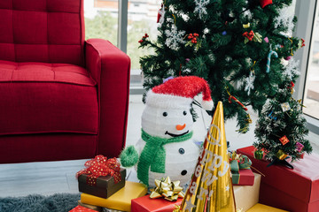 Snowman and golden cone placed on floor near stack of gift boxes under decorated Christmas tree in living room