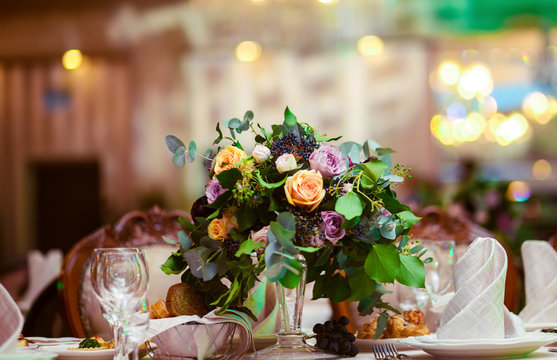 Beautiful flowers on table in wedding day. Decoration of wedding table with flowers. Beautiful wedding restaurant for marriage. Colorful decoration for celebration. Bouquet and flowers in hall.