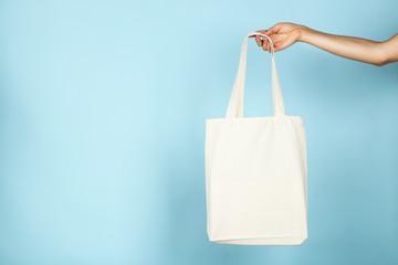 Female hand holding white cotton eco bag on blue background