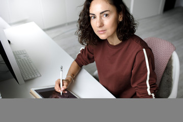 Female web designer using tablet at home, looking at camera