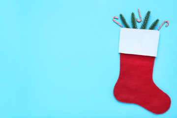 Red christmas stocking with fir tree branches and candy canes on blue background