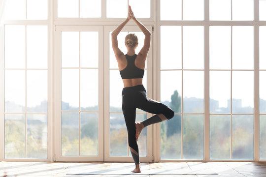 Young woman doing yoga at studio, tree pose