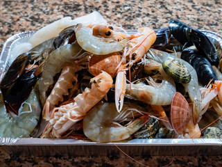 Mix of mussels, clams, shrimps and sea cicadas. Tray of fresh mixed fish ready to be cooked. Italian mediterranean Organic Food.