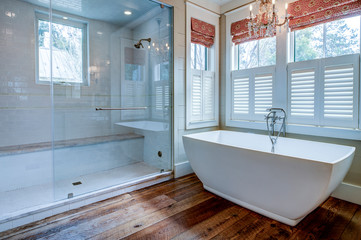 Beautiful luxury bathroom with large white tub and white tile walk in shower.