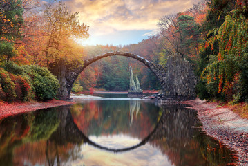 Photo sur Plexiglas Brun profond Fantastic Autumn Landscape. Amazing sunset With colorful sky in Azalea and Rhododendron Park Kromlau .Rakotz Bridge, Rakotzbrucke Devil's Bridge in Kromlau, Saxony, Germany.