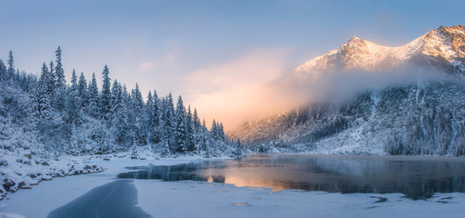 Spoed Foto op Canvas Bergen Sunrise in winter mountains. Mountain reflected in ice lake in morning sunlight. Amazing panoramic nature landscape in mountain valley.