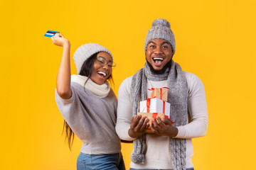 Excited afro couple holding xmas gifts, demonstrating credit card