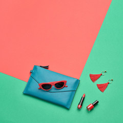 Fashion party girl Flat lay. Minimal. Woman Essentials accessories. Trendy Clutch, sunglasses, cosmetic makeup. Coloful coral geometry Set. Creative pop art concept, vibrant fashionable color