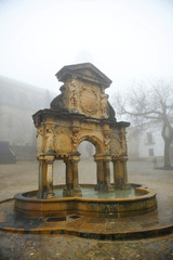 Renaissance fountain of Santa Maria a foggy day in Baeza, Andalusia, Spain.