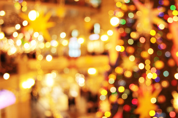 Blurred holyday Christmas tree with bright garland lights in a big department store. Abstract new...