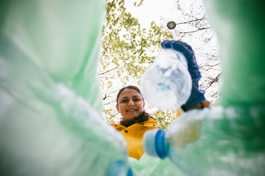 Volunteer with garbage bags collecting plastic bottles. Low angle view of girl cleaning park