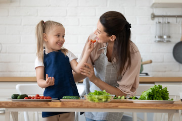 Funny kid daughter having fun with mother prepare healthy salad