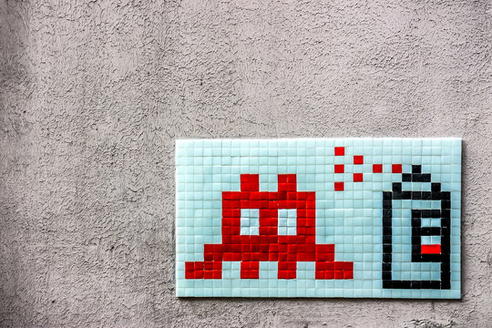 a graffiti mosaic depicting a spray can and an icon of space invaders on a wall of paris