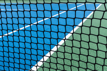 Detail of a Blue Tennis court with black net on Outdoor