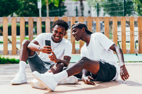 Cheerful amusing African American sportsmen surfing mobile phone comfortable placed on playground in bright day