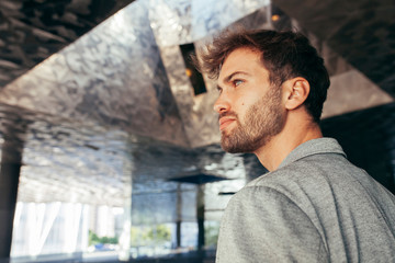 Fashionable handsome man in stylish gray jacket and casual t shirt standing and looking away with reflected modern wall on background