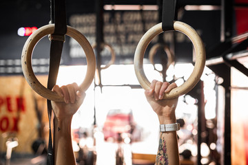 Crop tattooed strong hands of unrecognizable person holding gymnastic rings in fitness club during acrobatic exercise