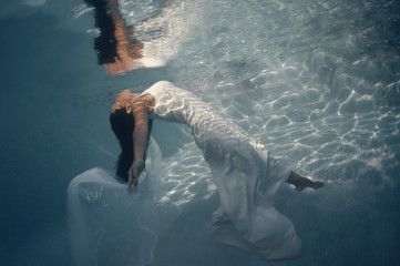 Side view of beautiful long haired brunette in long white wedding dress with veil floating underwater with outstretched arms