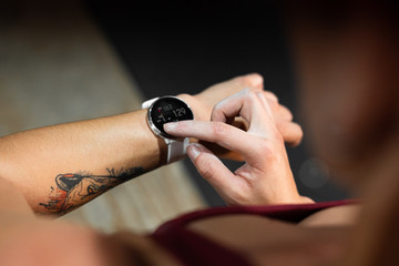 From above of crop person tattooed hand with modern tracker watch and numbers on black screen during checking time of sport exercise