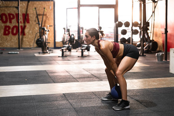 Side view of powerful sportive female athlete lifting kettlebell with both arms above head during physical training in fitness club