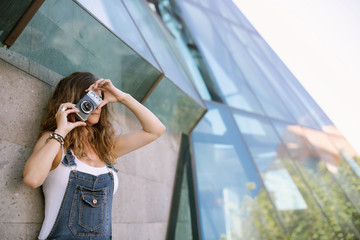 Young enthusiastic woman capturing moment taking picture on camera on background of glass architecture