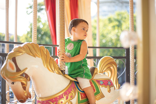 Pensive curious child in green casual clothes looking away while riding fabulous carnival horse alone in amusement park in sunny day