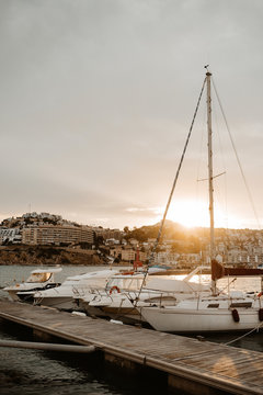 Sea port with white yachts and boats in city with buildings on hills at beautiful sunset with cloudy sky