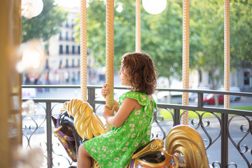 Charming little girl on colorful moving merry go round at fair in daylight