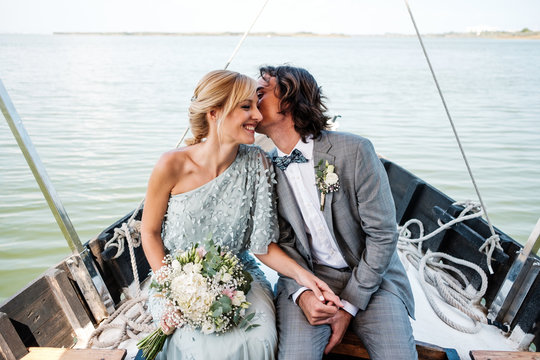 Satisfied married lovers in wedding clothing kissing while relaxing on boat with sea on background