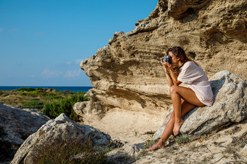 Side view of tanned slim woman in white shirt taking photo comfortably placing on stony rock in bright day