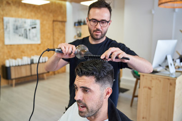Stock photo of a barber drying hair with a comb and a hairdryer in a barber shop. Barbershop and lifestyle
