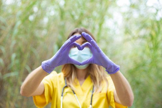 Mujer enfermera joven vestida con uniforme amarillo, guantes y mascarilla, forma un corazón con sus manos en entorno de naturaleza