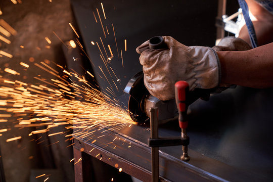 Cropped hands of workman in protective glasses and gloves cutting metal with grinder with flying sparks while working in workshop