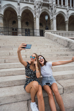 Active smiling women in sunglasses hugging and  taking selfie on background of ancient building in Budapest