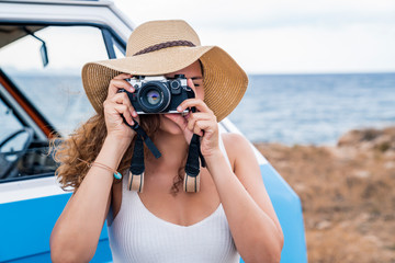 Active enthusiastic lady in hat photographing on camera in hands nearby blue car on beach