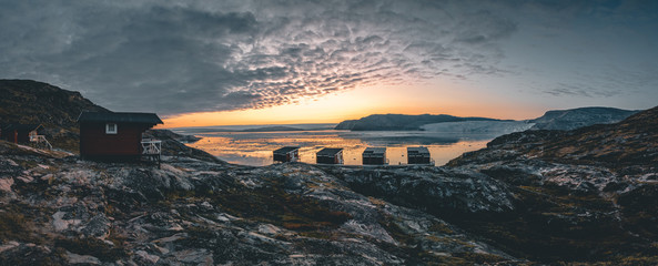Panoramic image of Camp Eqi at Eqip Sermia Glacier in Greenland. nature landscape with lodge cabins. Midnight sun and pink sky. Tourist destination Eqi glacier in West Greenland AKA Ilulissat and