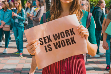 "The phrase "" Sex work is work "" drawn on the banner in the crowded city. Prostitution services. Rights. Escort"